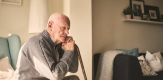 Thoughtful elderly man sitting alone at home with his walking cane