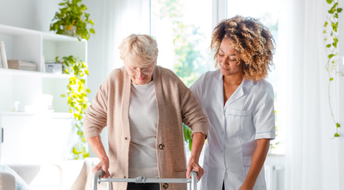 African american female home nurse supporting senior woman in using mobility walker at home.