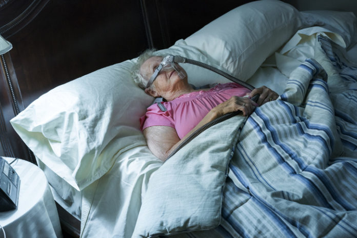 Senior age Caucasian woman sleeps in bed wearing a C-Pap machine to aid her breathing and supplement oxygen, Minnesota, USA